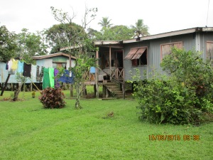 The houses are built on stilts because the village is on an island surrounded by a river that floods frequently.