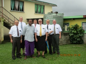 Our husbands and Bishop Savu by a water tank donated by the Church.