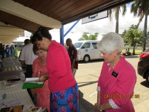Self Reliance missionary, Sister Smith, and stake RS president Sister Shaw, gathering up booklets for the Minister of Women, children & Poverty Alleviation